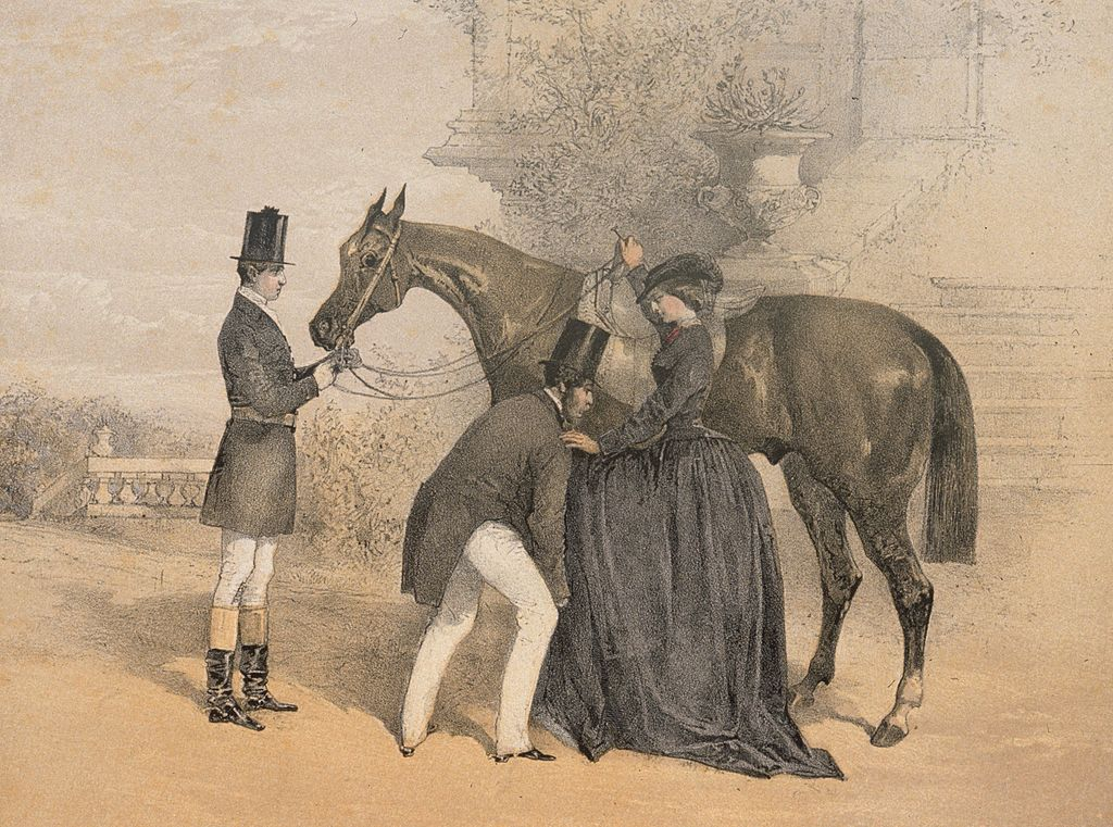 1857: One man holds the horse's head while another helps a Victorian lady onto its back. Original Publication: From 'The Ladies Equestrian Guide' by Mrs Stirling Clarke.
