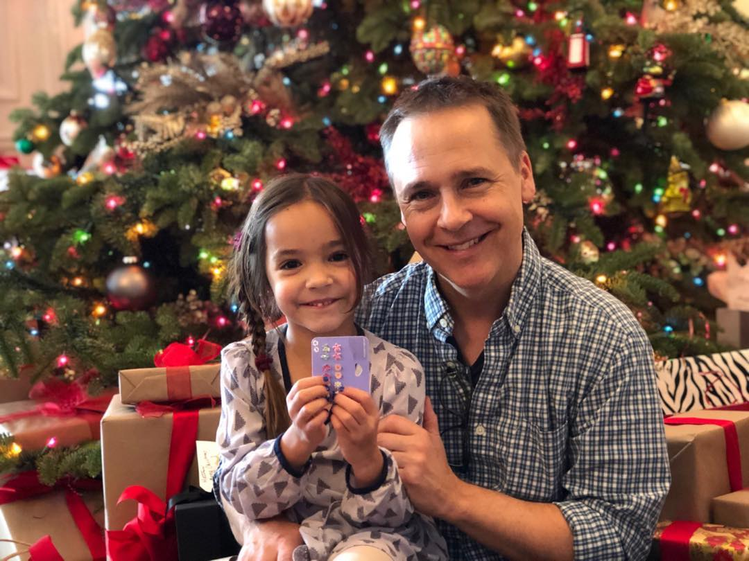 chad lowe and his daughter in front of a christmas tree