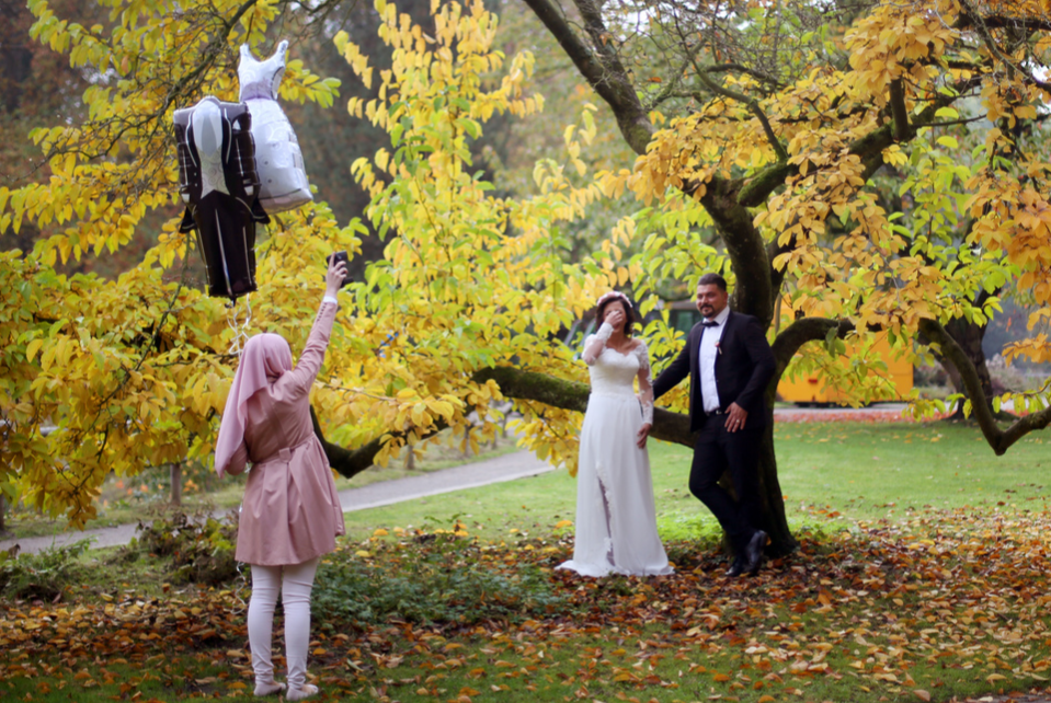 A wedding couple posing in front of a tree during an autumn wedding