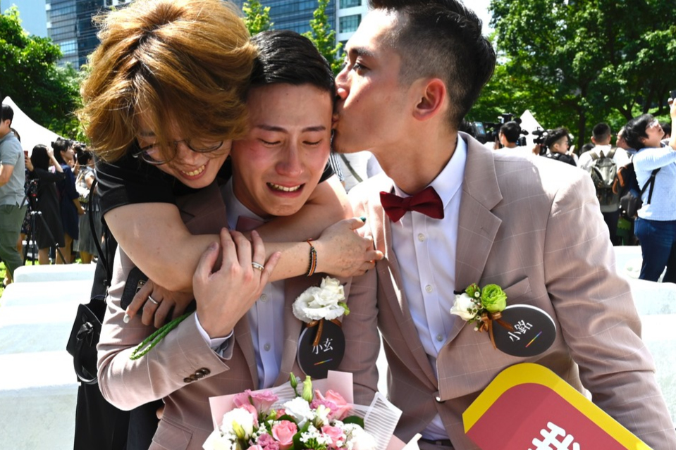 Man comforted by his partner and a friend during a wedding ceremony