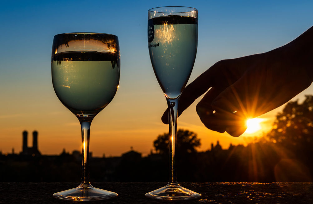 At sunset, two glasses of white wine stand on the wall