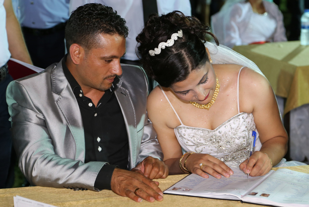 A Turkish couple signs the wedding book following a mass wedding ceremony organized by the local government and a non-profit organization Nehir Foundation, for some 90 low-income couples