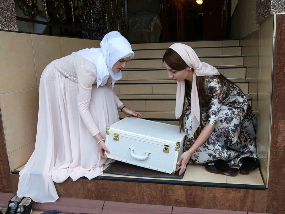 Relatives and family members with a suitcase of the bride's dowry on the day of wedding in Chechen capital Grozny