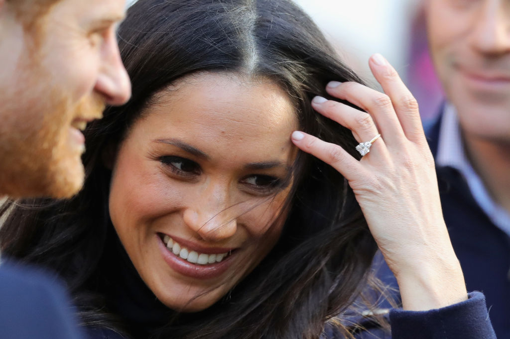 Prince Harry and Meghan Markle while Markle shows her diamond ring