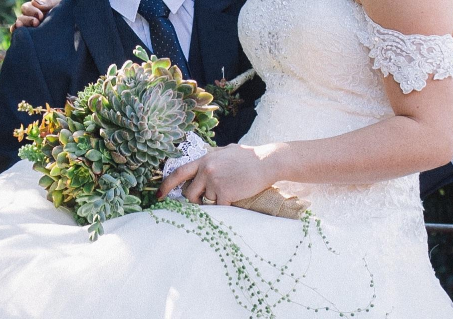 Bride carrying succulent bouquet while hugging the groom.
