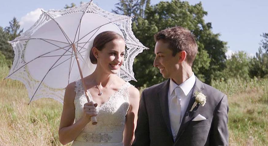 bride carrying a white lace parasol walking with green