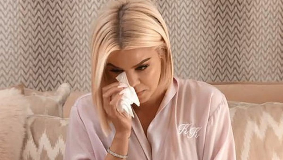 khloe kardashian crying on bed in pink robe