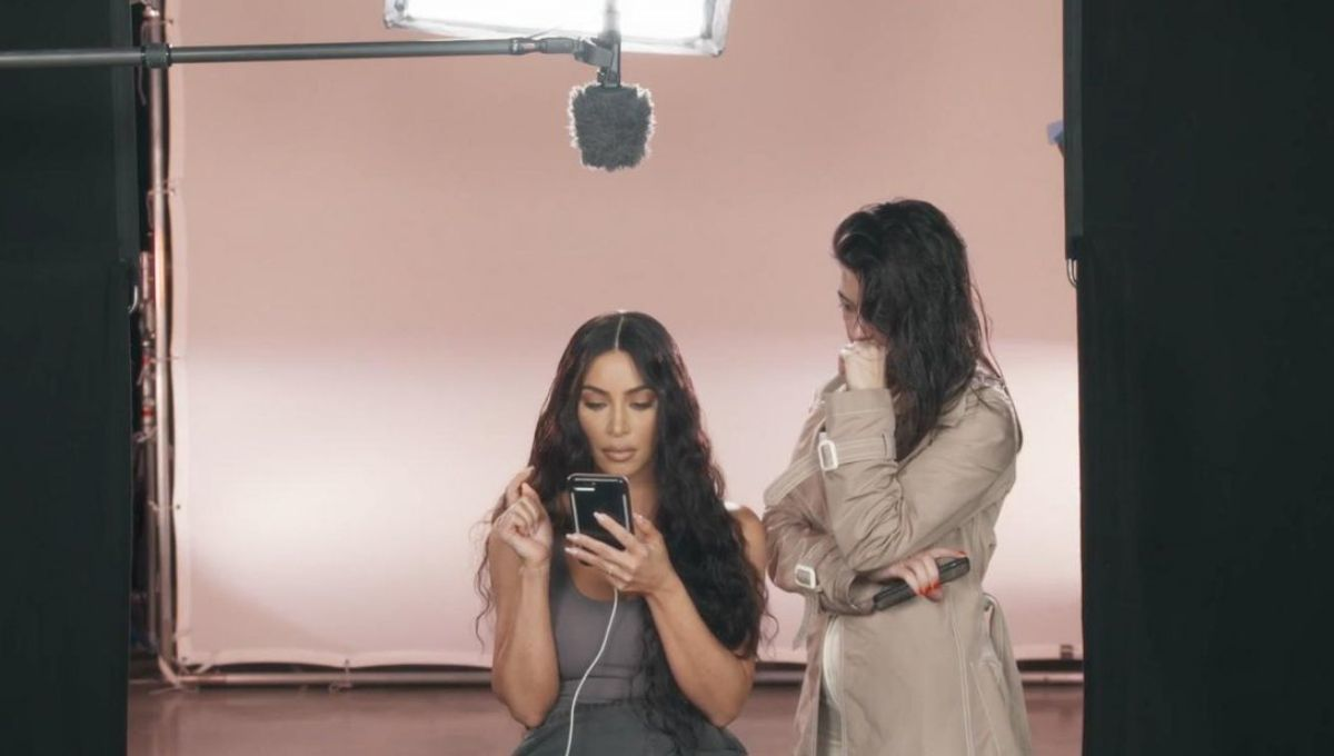 kim and kourtney sitting and looking at phone