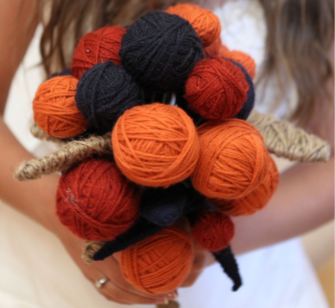 black and orange yarn ball bouquet held by a bride