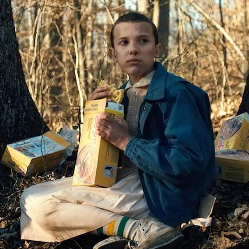 millie bobby brown in character as eleven, eating waffles