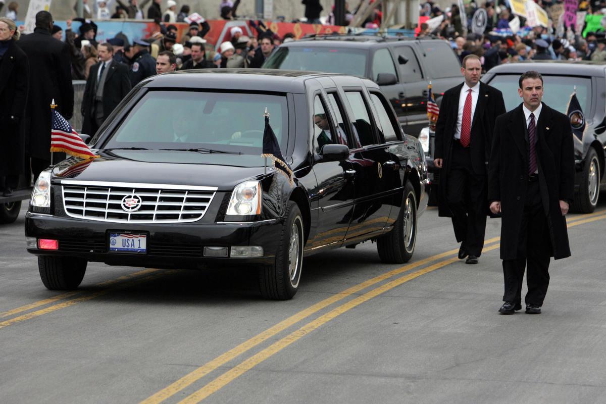 presidential limousine with secret service walking beside