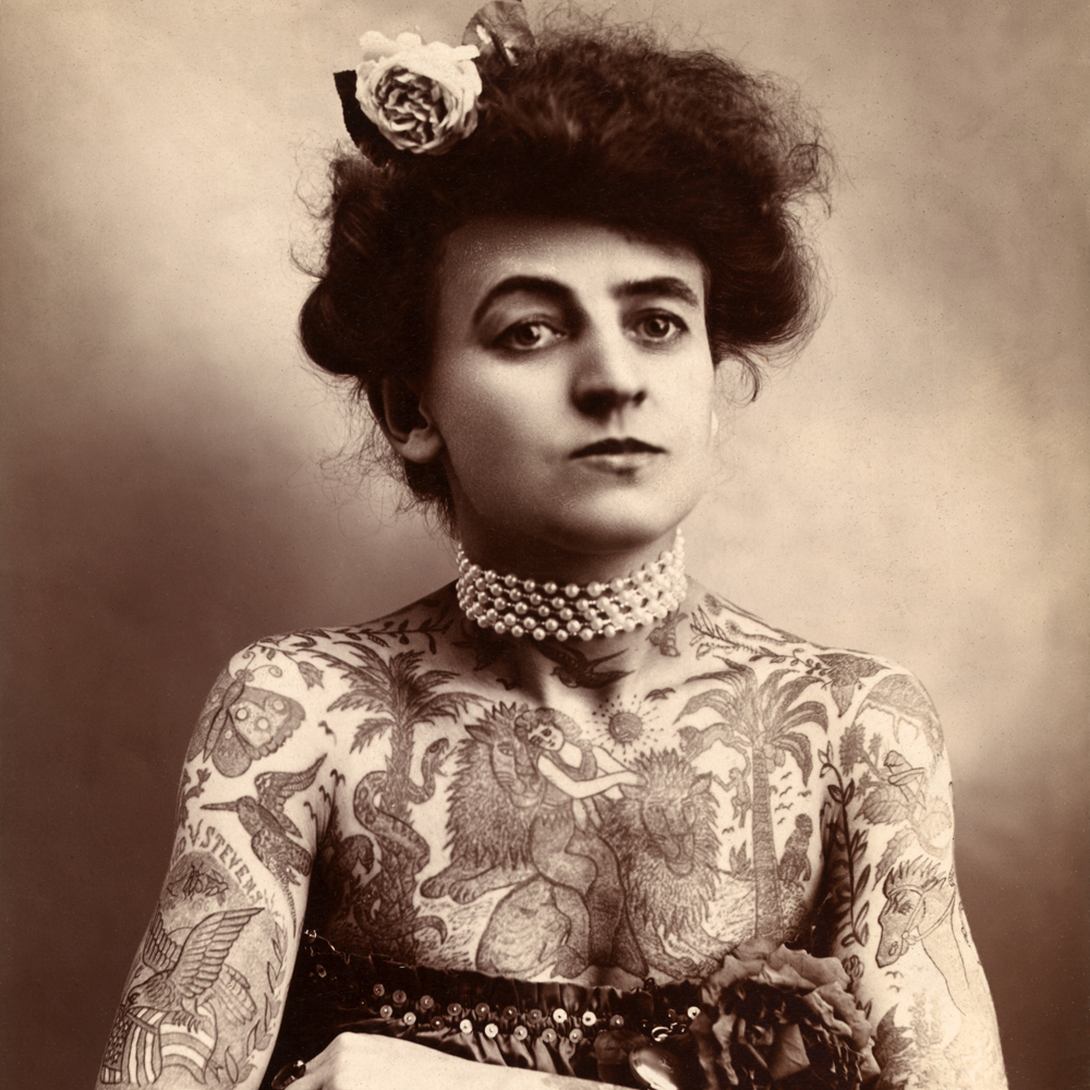 Early photograph of a woman covered with extensive tattoos; toned photograph, 1907-566420285