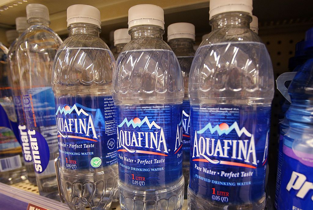 Bottle of Pepsi's Aquafina water sits on a shelf next to other brands of bottled water at a Walgreens store-75817758