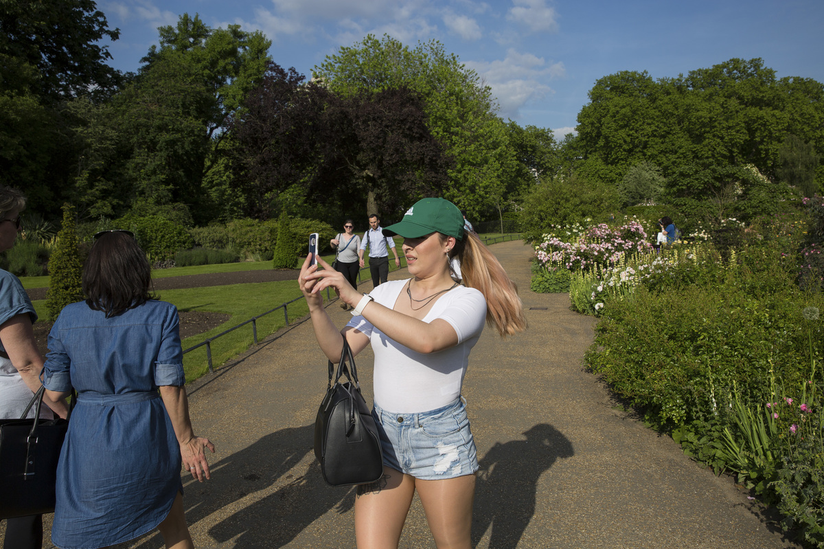 A girl takes photos on her mobiles phone in Hyde Park wild gardens on 24th May 2017 in London, United Kingdom.