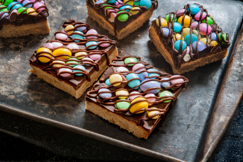 two colorful shortbread candy bars drizzled with chocolate on a baking sheet