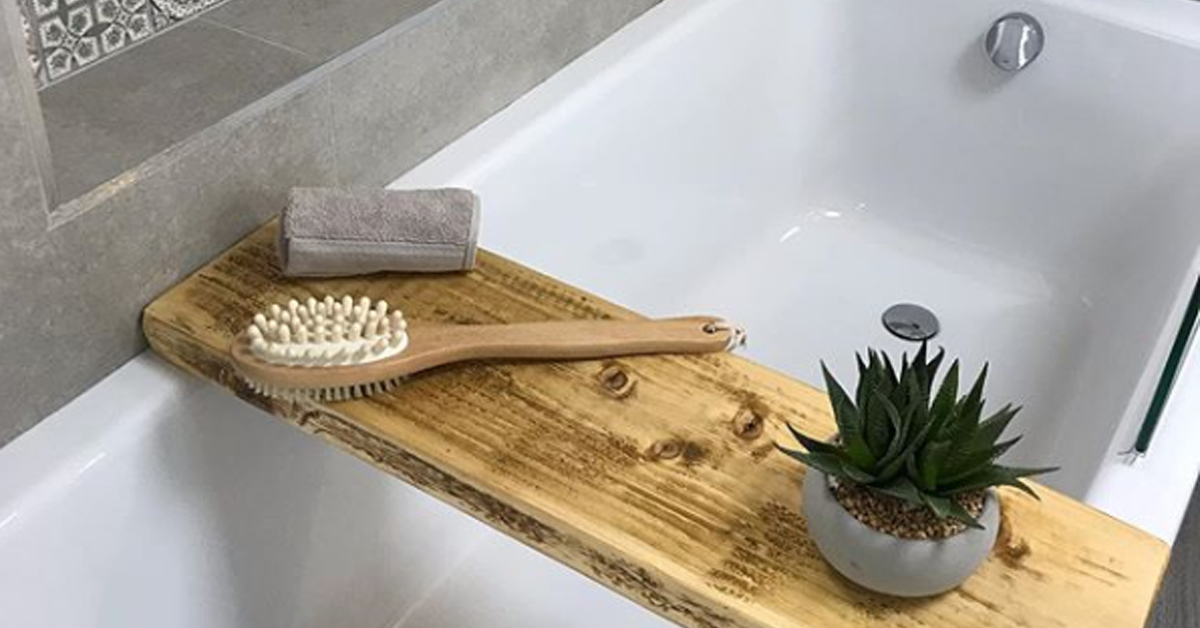 a wooden bath tray with a succulent, brush, and towel over a bathtub
