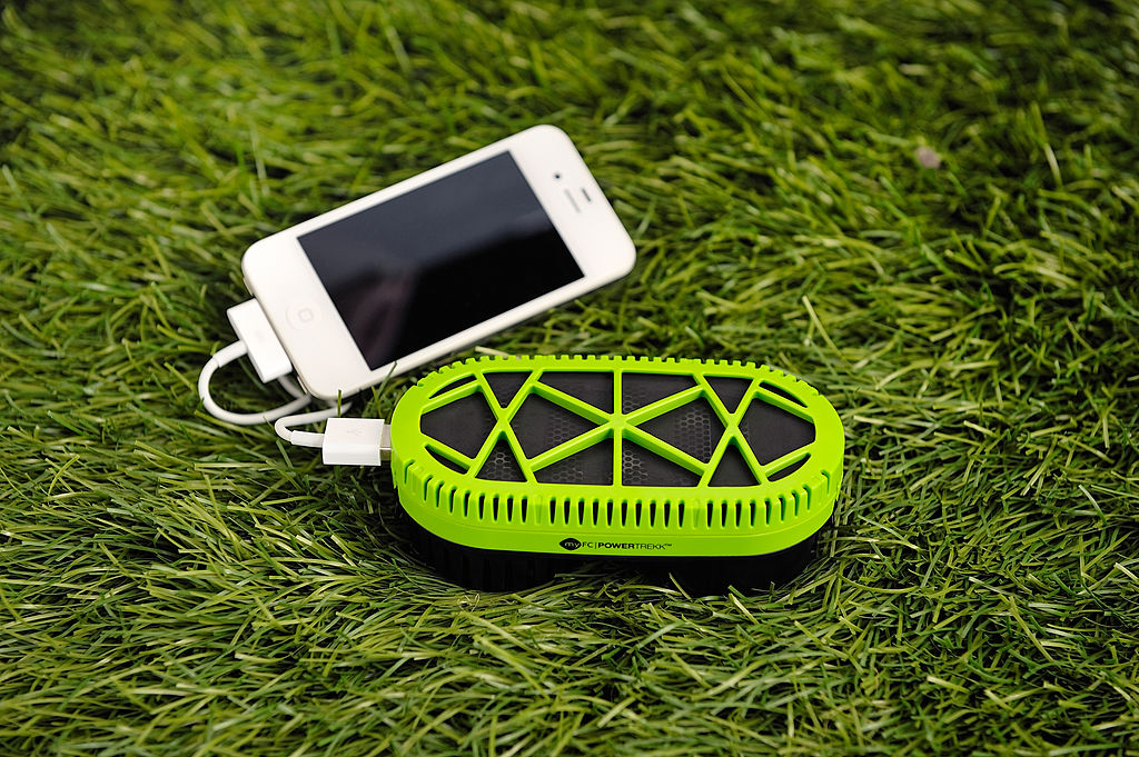 iphone plugged into a phone charger on the grass