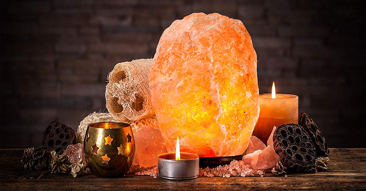 a himalayan salt lamp on a table with candles
