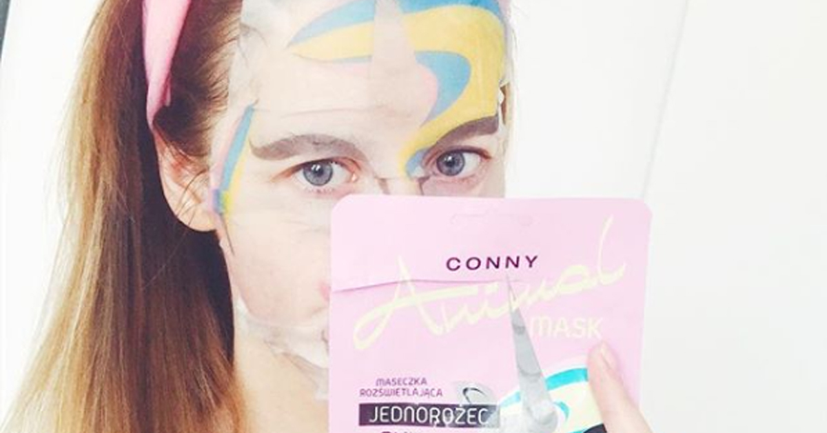a girl wearing a unicorn sheet mask and holding up the packaging