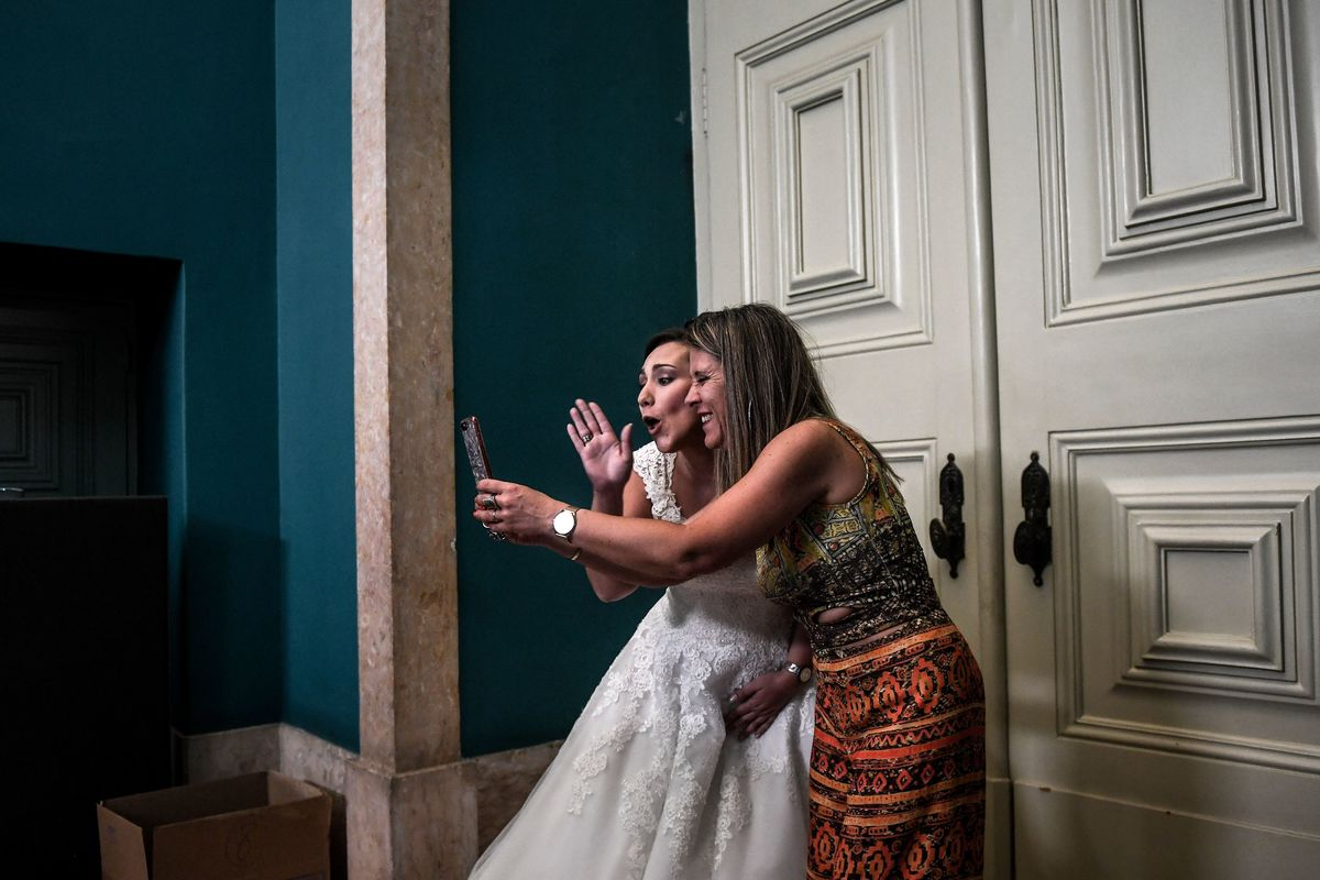 A bride takes a selfie photo before celebrating a multiple wedding ceremony in Lisbon