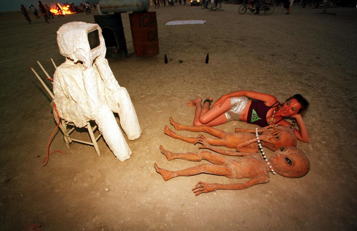 woman and aliens lying in front of a tv