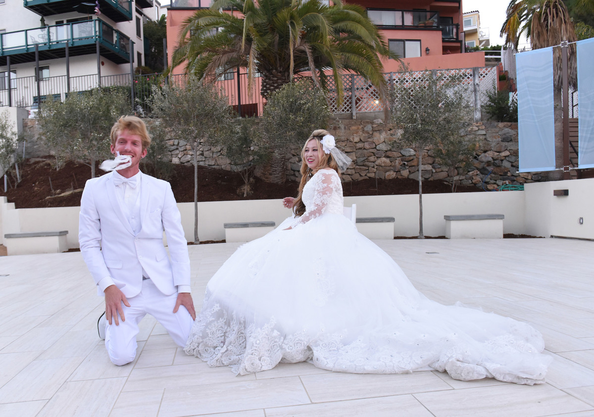 Justin Moore Aoki throws Alice Aoki's garter at their dessert reception at the Catalina Island Museum
