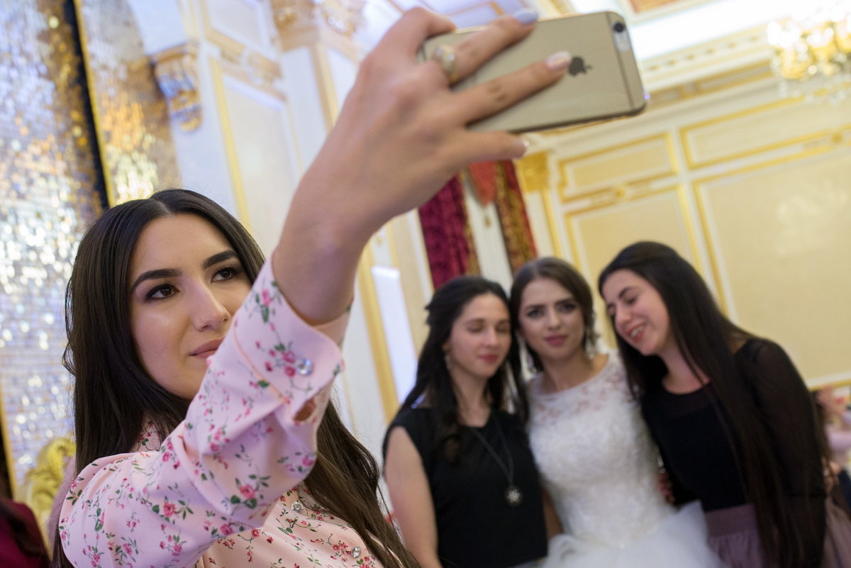 A bride poses for a selfie with guests during a wedding celebration.