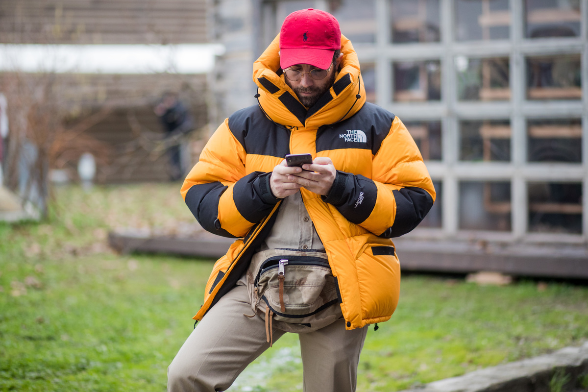 a man in a north face jacket on his phone