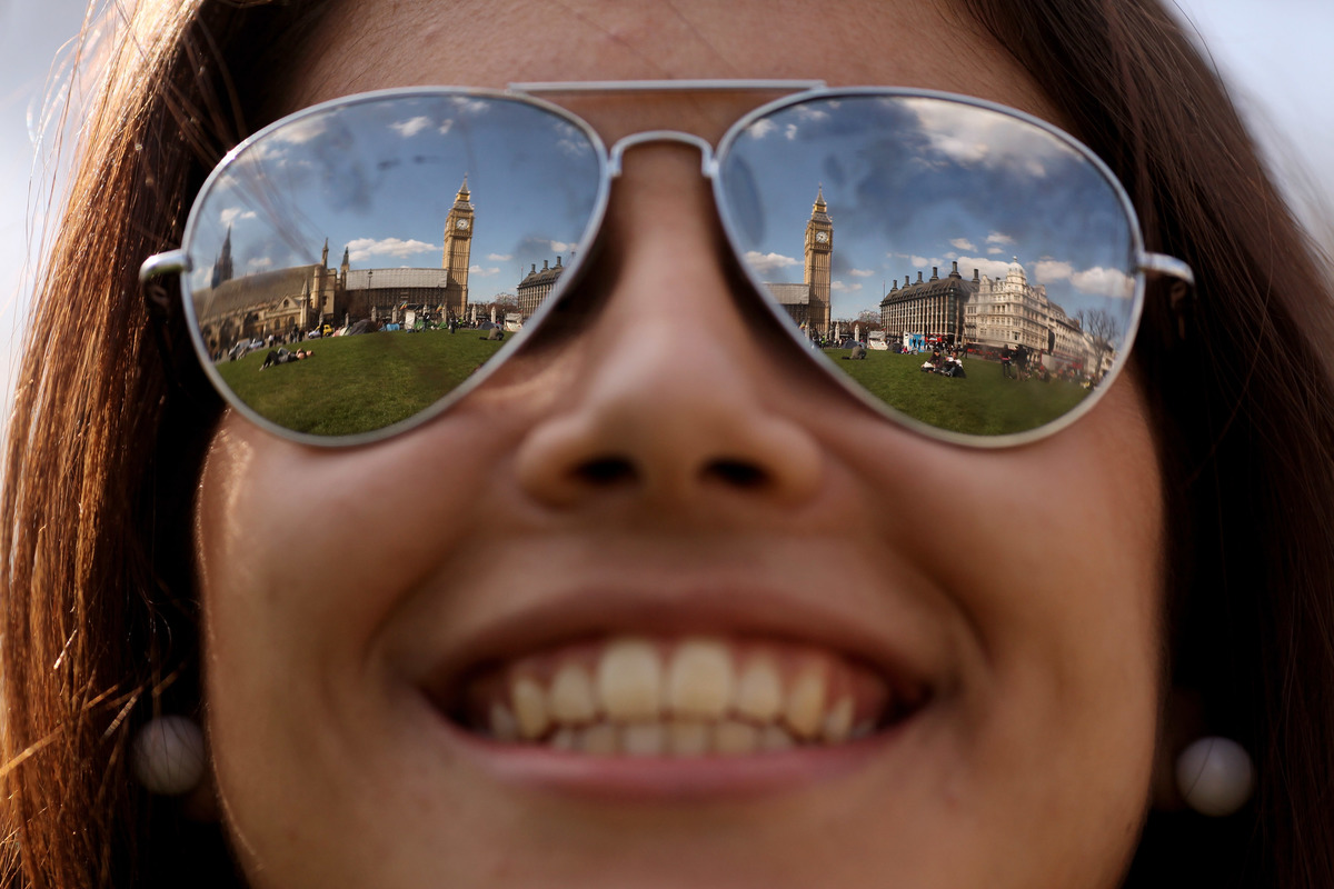 A tourist enjoys warm spring weather in Parliament Square on April 8, 2010 in London, England.