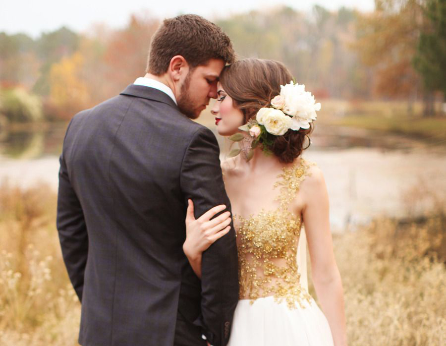 Newlywed couple pose in a golden field