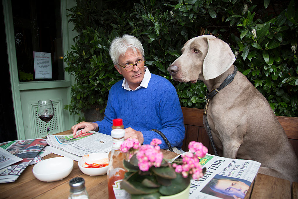 Man enjoying the Sunday newspapers with his Weimaraner dog Max