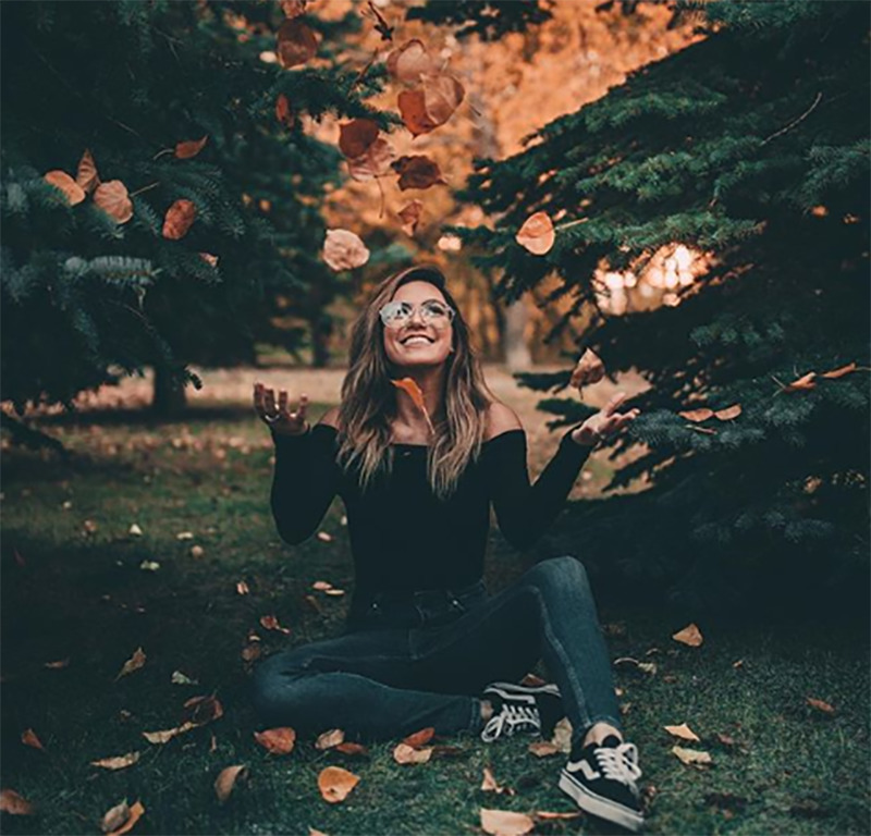 A smiling woman sits on the grass and throws fallen leaves in the air