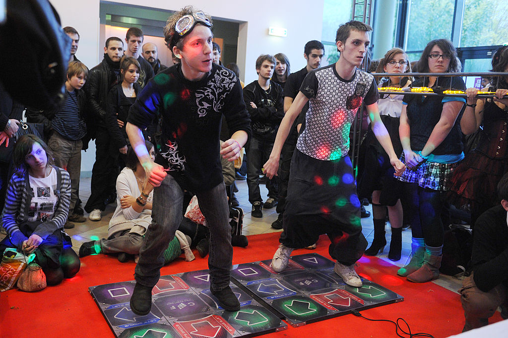Two male teenagers play DDR against each other in a crowd of onlookers