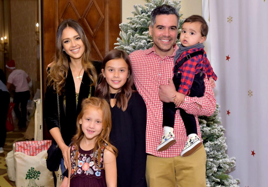 Jessica poses with her husband and their three children at a holiday party