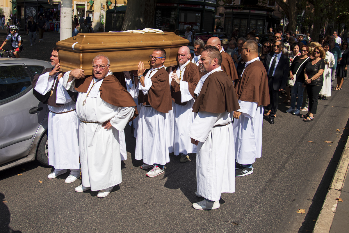 The confreres carry a coffin during a funeral in Rome, Italy