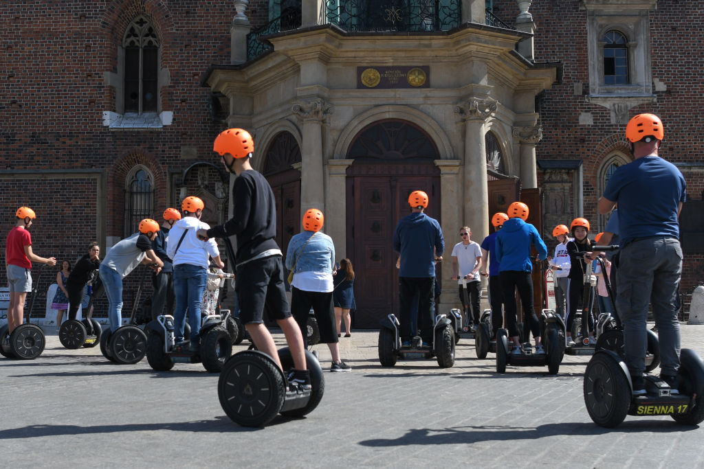 People ride segways outdoors