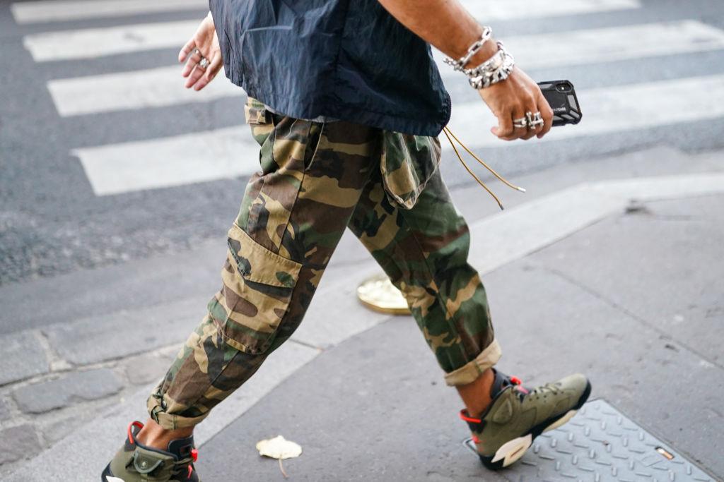 A man walks in camo pants near a street
