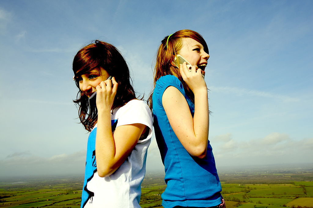 Two young teenage girls stand back to back while talking on their cellphones