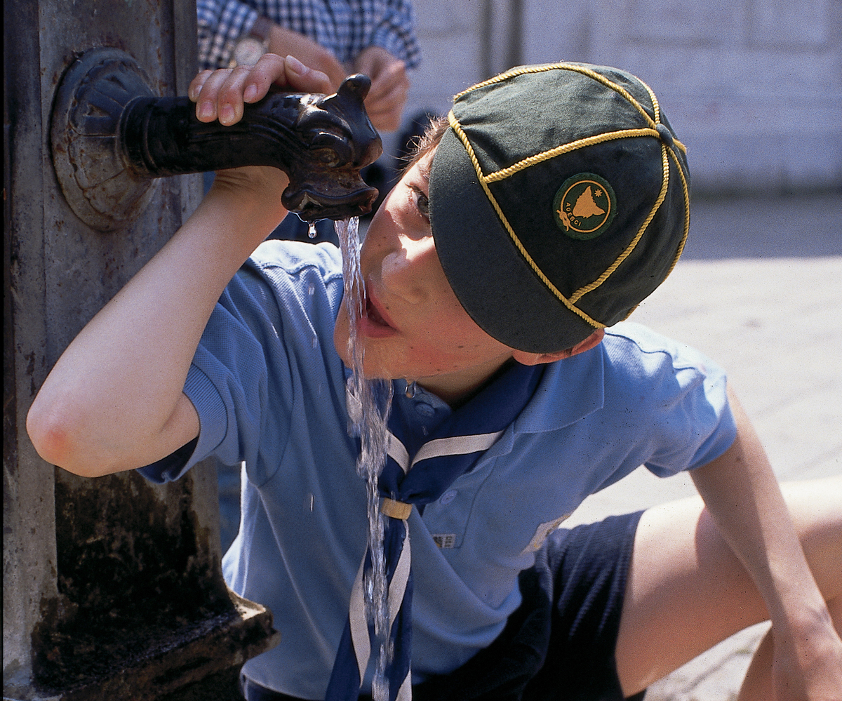 Italian boy (wearing an Association of Catholic Guides and Scoutsof Italy uniform, AGESCI) drinking water, Venice, Italy.