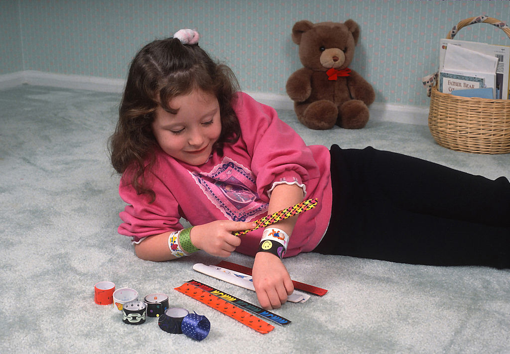 A little girl lays on the floor, putting on her slap bracelets