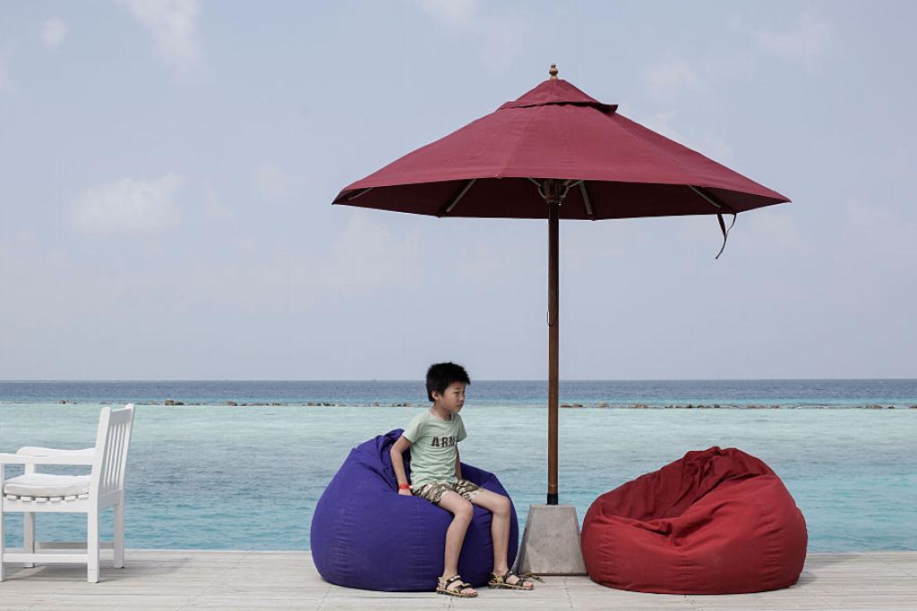 A boy sits on a bean bag on a boardwalk