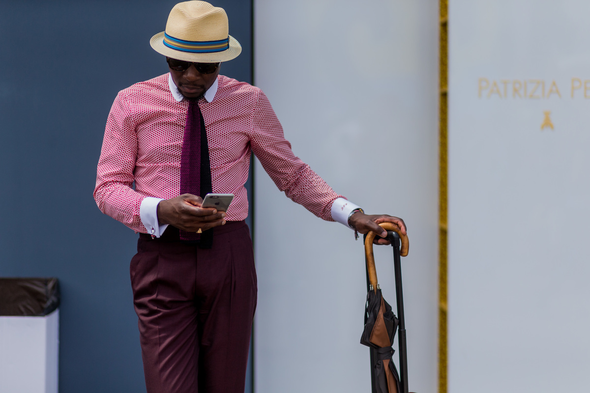 A guest with a suitcase and pink button shirt during Pitti Uomo 90