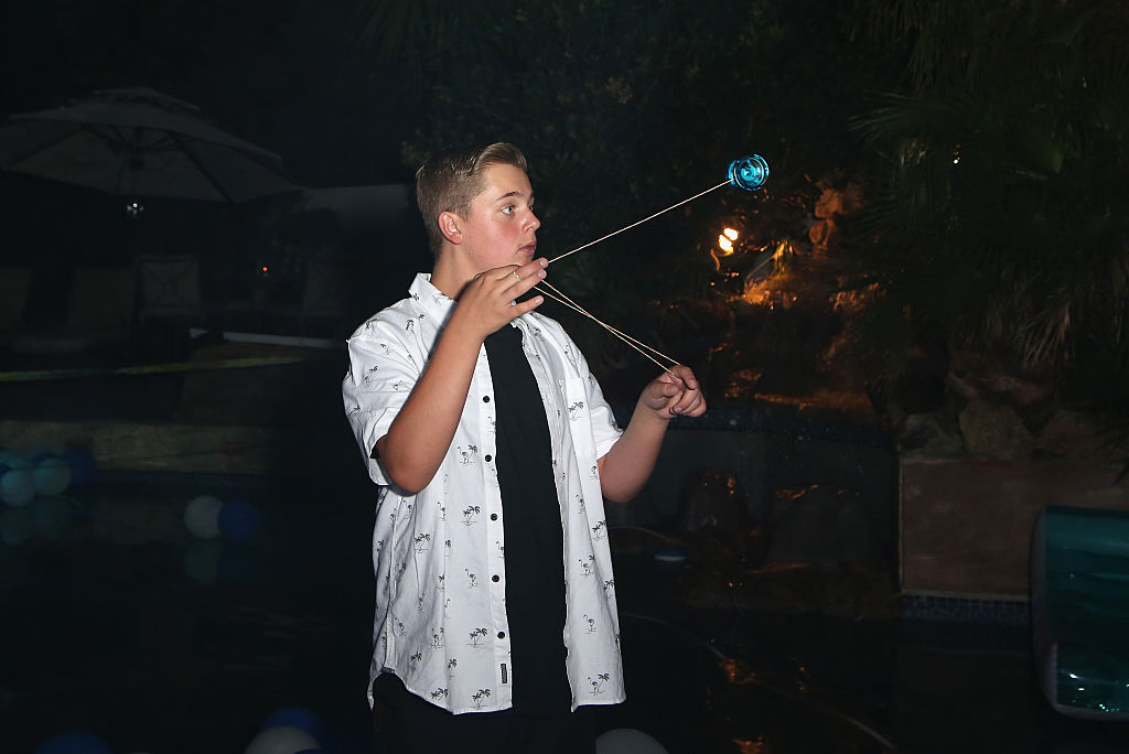 A teen plays with a yoyo