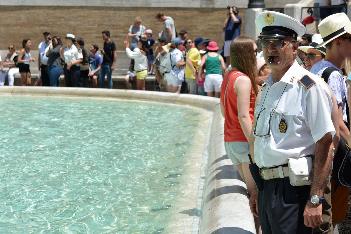 Officials warn people, who sit near of the Trevi Fountain in Rome, Italy