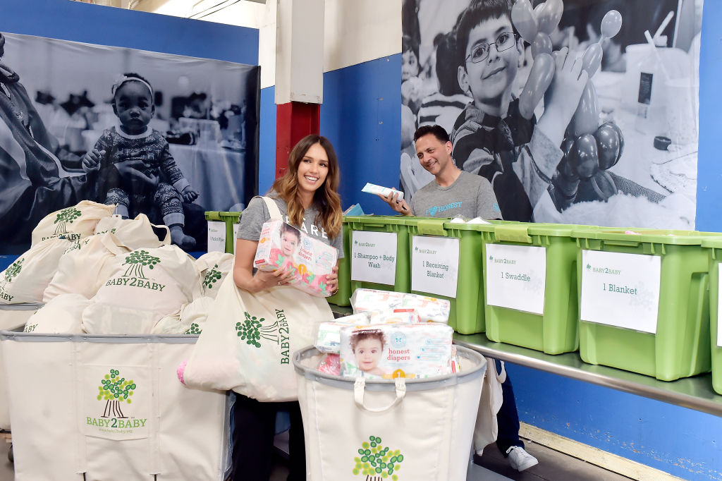 Jessica holds honest diapers at a Baby2Baby event