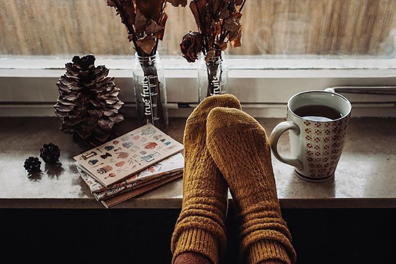 Feet in thick socks are perched on a window sill with a mug of coffee