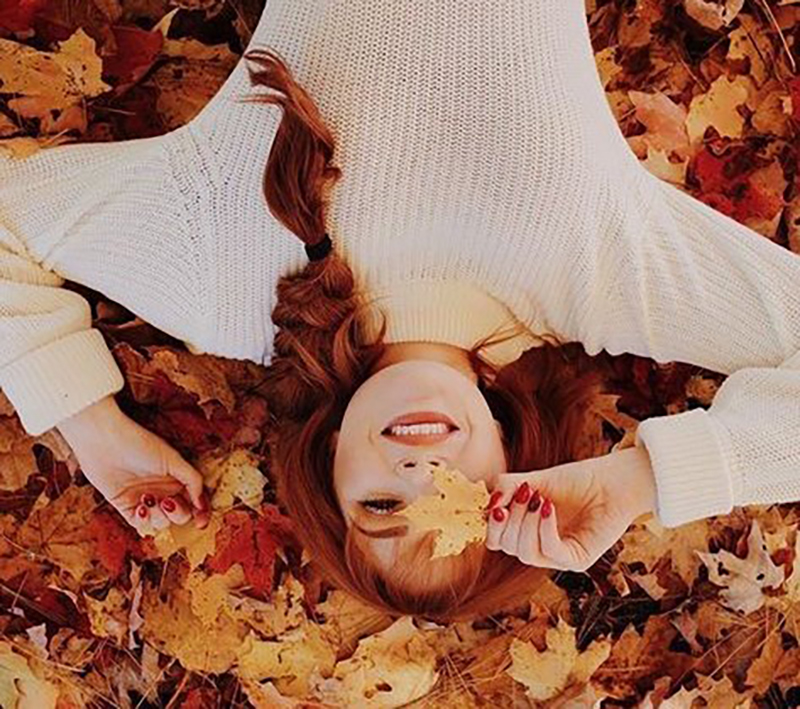 A girl is photographed from above laying in a bed of leaves and holding one leaf over one eye
