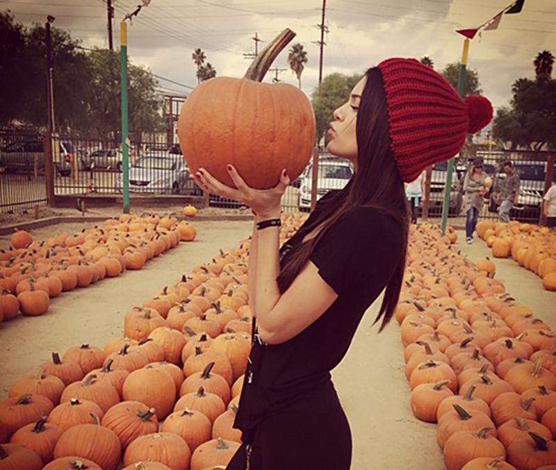 A girl puckers her lips towards the pumpkin she hold in front of her face at a pumpkin patch
