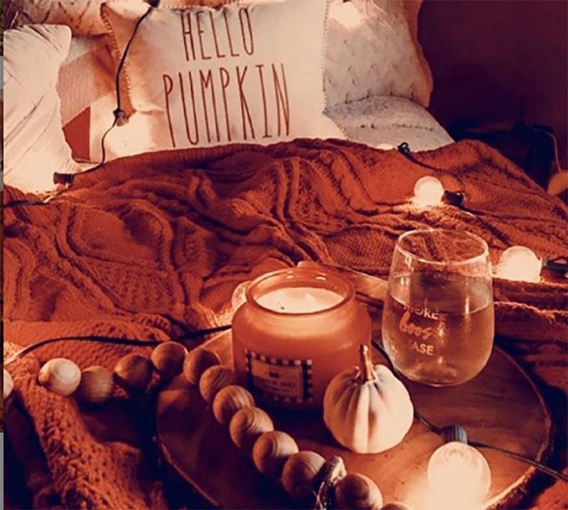 A bed is covered with autumn inspired decor and a string of lights