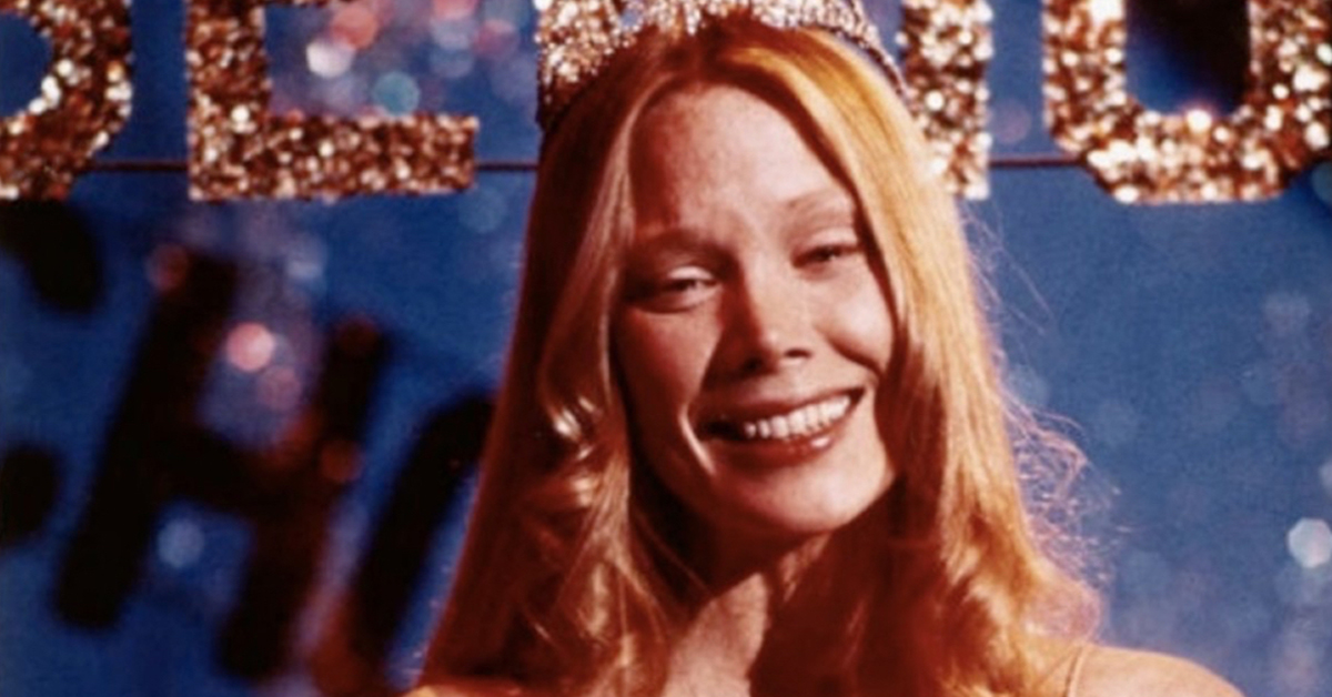 sissy spacek wearing a prom dress and holding flowers